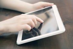 Femelle tenant et touchant une Tablette blanche vide d'affaires sur un bureau Photo stock