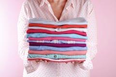 Femelle tenant une pile des vêtements pliés, unisexe pour l'homme et la femme, la couleur différente et le matériel Concept de pr photo stock