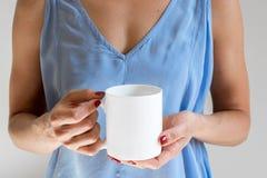 Femelle tenant une tasse de café, photographie courante dénommée de maquette Photo libre de droits