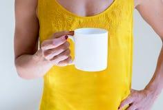 Femelle tenant une tasse de café, photographie courante dénommée de maquette Photo stock