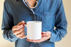 Femelle tenant une tasse de café, photographie courante dénommée de maquette Images stock