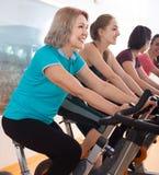 Femelles actives de la formation différente d'âge sur des vélos d'exercice Photos stock