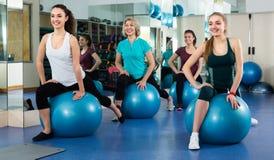 Femelles avec la boule de forme physique au gymnase image stock
