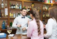 Femelles causant et buvant du vin dans la barre Image libre de droits