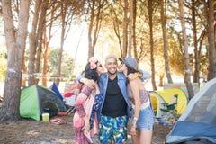 Femelles embrassant les amis masculins se tenant au terrain de camping Photos libres de droits