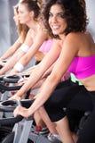 Femelles faisant un cycle dans la classe de rotation en gymnastique Photographie stock libre de droits