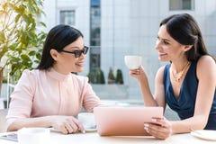 Femelles gaies parlant au bureau en café Photo stock