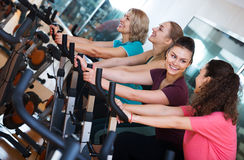 Femelles s'exerçant sur des vélos d'exercice Photo stock