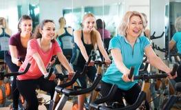 Femelles s'exerçant sur des vélos d'exercice Photo libre de droits