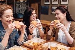 Femelles satisfaisantes mangeant les hamburgers frais Photographie stock libre de droits