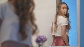 Femenino ansioso mirando su cuerpo en espejo metrajes