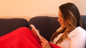 Femenino disfrutando de su tiempo apagado, libro de lectura de su tableta en sala de estar