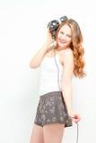 Femenino divirtiéndose que escucha los auriculares Imagen de archivo libre de regalías