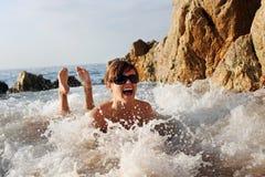 Femenino joven divirtiéndose en la orilla de mar Fotos de archivo