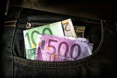 Femhundra, tvåhundra och hundra eurosedel i facket av jeans royaltyfri fotografi