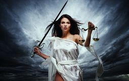 Femida, Goddess of Justice. With scales and sword against dramatic stormy sky