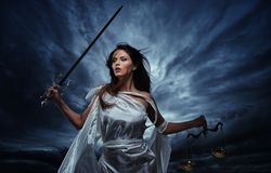 Femida, Goddess of Justice. With scales and sword against dramatic stormy sky Royalty Free Stock Photo