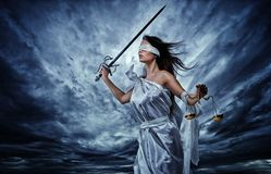 Femida, Goddess of Justice. With scales and sword wearing blindfold against dramatic stormy sky stock photo