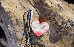 The feminine art project. Three well used paint brushes next to heart shaped pink painted box on a big old and dry log Stock Image