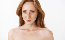 Feminine attractive adult and slim redhead female with freckles and natural ginger hair standing naked over white royalty free stock photography