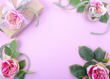 Feminine background with gift and silk roses Stock Image