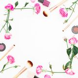 Feminine beauty composition with pink roses and cosmetics on white background. Beauty concept, floral frame. Flat lay, Top view. Stock Photography