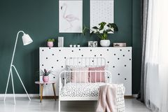 Feminine bedroom interior with a bed, bedside table, lamp, plant. S and flamingo poster royalty free stock image