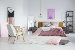 Feminine bedroom with woolen blanket. Spacious, feminine bedroom interior with cozy woolen blanket and pink tulle dress Stock Photo