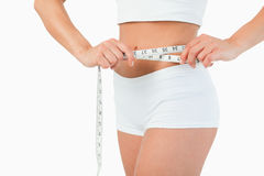 Feminine body with a measuring tape Royalty Free Stock Images