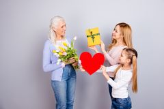 Feminine care trust positivity tenderness people three concept. Pretty mom cute schoolgirl are giving present yellow white tulips to cheerful joyful excited royalty free stock photo