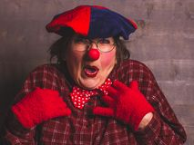 Feminine clown comedy emotional expression with red nose, carnival kids concept. Woman emotional funny cheerful clown with glasses, red nose, shirt, hat and Royalty Free Stock Images