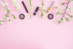 Feminine desk with cosmetic: lipstick, shadows, mascara and white spring flowers on pink background. Flat lay, top view. Beauty co Stock Photography