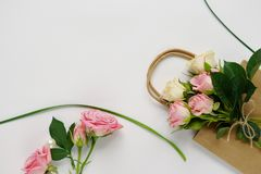 Feminine desk with pink roses, green leaves, and gift bag on white background. Flat lay, top view. Flower background. Women`s day,. Feminine desk with pink roses Royalty Free Stock Images