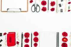 Feminine desk work space with clipboard, notebook, red flowers and accessories on white background. Border frame. Flat lay, top vi. Feminine desk work space with Stock Photos