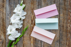 Feminine desk workspace. Envelope and gladiolus on wooden background top view.  Royalty Free Stock Image