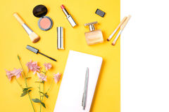 Feminine desk workspace flat lay with diary, makeup products, perfume Royalty Free Stock Photos