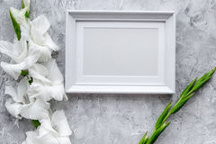 Feminine desk workspace. Frame for photo and gladiolus on grey stone background top view mockup Royalty Free Stock Photos