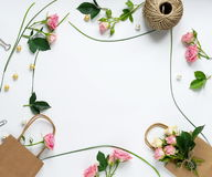 Feminine desk workspace frame. With pink roses, green leaves, and gift bags on white background. Flat lay, top view. Flower background. Women`s day, mother`s Stock Photography