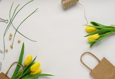 Feminine desk workspace frame. Feminine desk frame with yellow tulips and gift bags on white background. Flat lay, top view. Flower background. Women`s day Stock Images