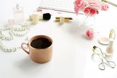 Feminine desk, workspace with laptop. Beauty blog concept. Female make up accessories, cup of cofee and bouquet of pink roses on white background. Flat lay, top Stock Photos