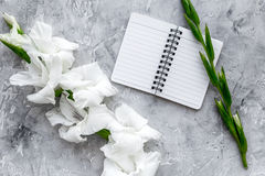 Feminine desk workspace. Notebook and gladiolus on grey stone background top view Stock Images