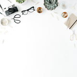 Feminine desk workspace with succulent, retro camera, scissors, diary, glasses and golden clips on white background Royalty Free Stock Images