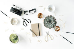 Feminine desk workspace with succulent, retro camera, scissors, diary, glasses and golden clips on white background Royalty Free Stock Image