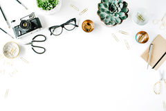 Feminine desk workspace with succulent, retro camera, scissors, diary, glasses and golden clips on white background Royalty Free Stock Photo