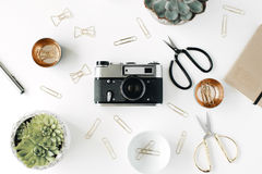 Feminine desk workspace with succulent, retro camera, scissors, diary and golden clips on white background Stock Image