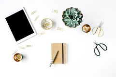 Feminine desk workspace with succulent, tablet, scissors, diary and golden clips Stock Photos