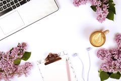 Top view of female worker desktop with laptop, flowers and different office supplies items. Feminine creative design workspace. Feminine desktop close up of stock photos