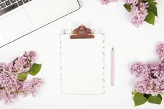 Top view of female worker desktop with laptop, flowers and different office supplies items. Feminine creative design workspace. Feminine desktop close up of Stock Images