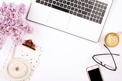 Top view of female worker desktop with laptop, flowers and different office supplies items. Feminine creative design workspace. Feminine desktop, close up of Royalty Free Stock Photo