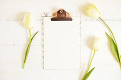 Feminine desktop composition with blank sheet clipboard & white tulips on wooden texture table background, copy space for text. Wo. Man workplace, flowers for stock images